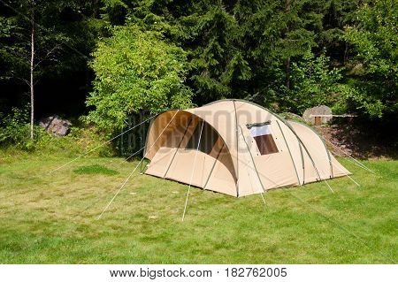 Tent on a grass campsite in a forest.