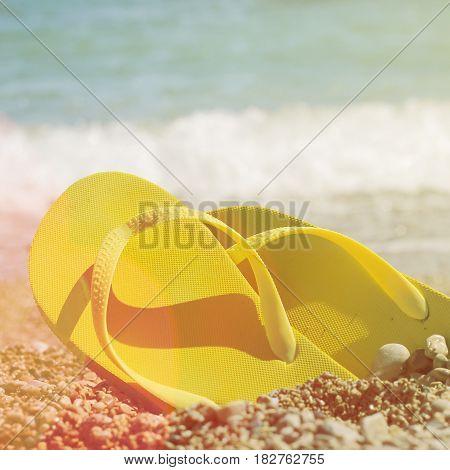 Pair Of Yellow Flip Flops On A Beach