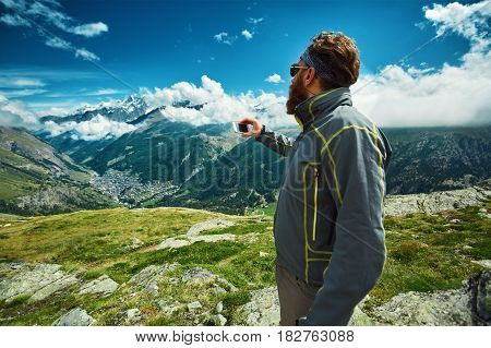 hiker at the top of a pass making selfie against snow capped mountains in Alps. Switzerland, Trek near Matterhorn mount.