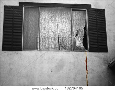 a broken window with something spilling out on to wall.