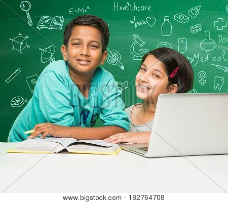 indian school kids using laptop in a classroom over green chalkboard background with doodles