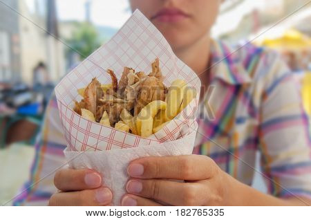 Girl holding Greek gyro with fries close up on table