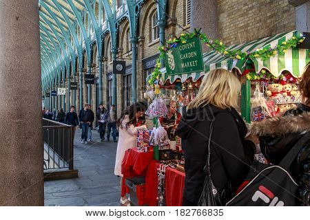 LONDON, GREAT BRITAIN - MAY 13, 2014: Unidentified tourists buy souvenirs in a well-known Covent Garden Market.