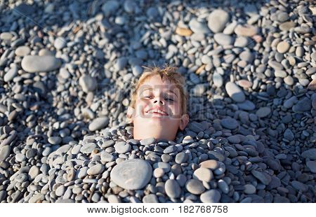 A young man with light red hair laughs. His body was buried under stones on the beach only his head sticking out the sun is shining