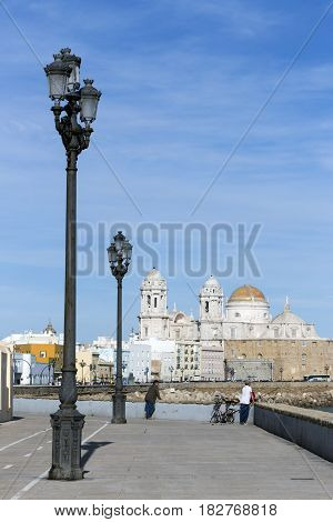 Cadiz SPAIN - March 31: Seafront and rail bicycle to the evening to the fund the cathedral of the holy cross In cadiz Andalusia Spain