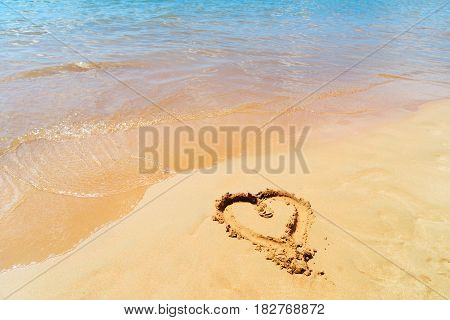 Heart draw in sand by tropical sea water