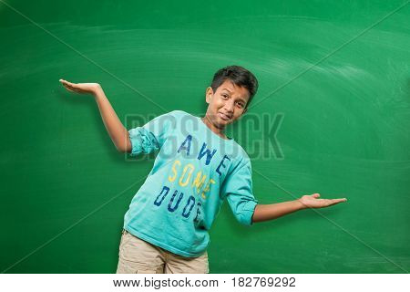 indian school kid or boy standing in front of green chalkboard with both hands stretched, presenting some concept with copy space