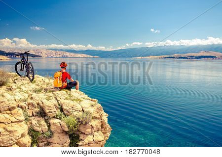 Mountain biker looking at view and traveling on bike in summer sea landscape. Man rider cycling MTB on rocky yellow trail. Fitness motivation inspiration in beautiful inspirational view.