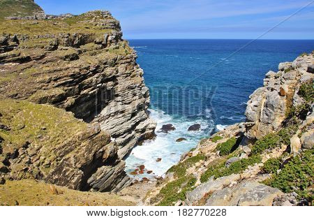 Aerial top view of sea waves hitting rocks next to Cape of Good Hope, Cape Town, South Africa.