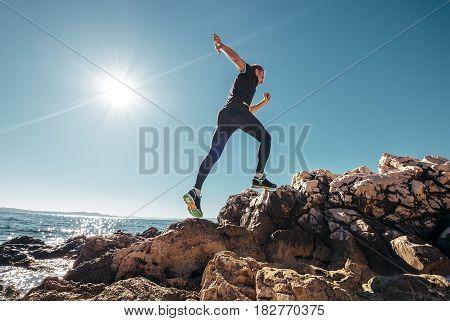 Running man on the rocky seaside .