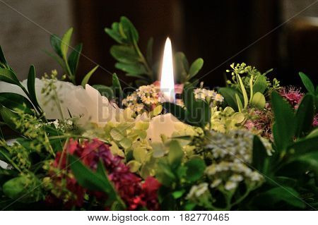Romantic candlelight on a flower arrangement - closeup