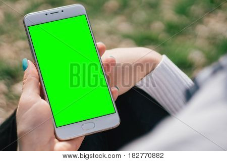 Girl with smartphone in hands with mock up green screen of blank screen sits in park on open space, screen for content integration. Hands holding gadget on blurred backdrop