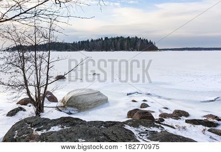 Small white oar boat upside down on frozen sea