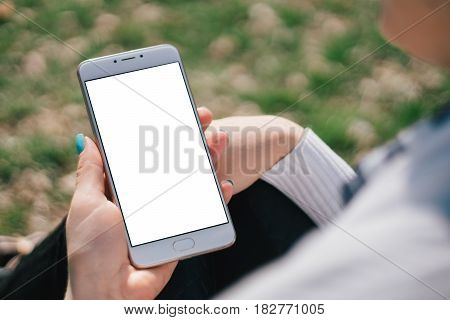 Girl with smartphone in hands with mock up white screen of blank screen sits in park on open space, screen for content integration. Hands holding gadget on blurred backdrop,