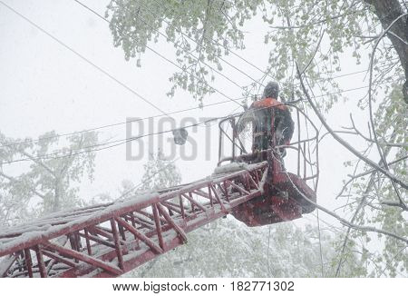 Chisinau, Republic Of Moldova - April 20, 2017: Electrician Stays On The Tower Pole And Repairs A Wi