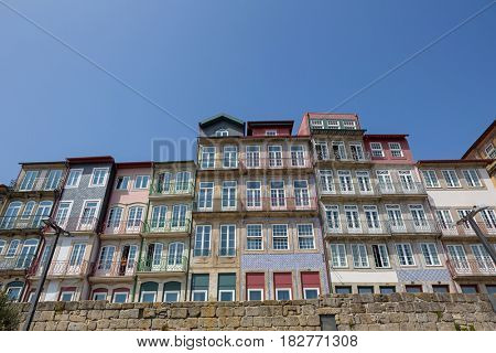 Porto, Portugal. April 17, 2017: The typical colorful buildings of the Ribeira District with shops, restaurants and bars built near the stone wall. Unesco World Heritage Site.