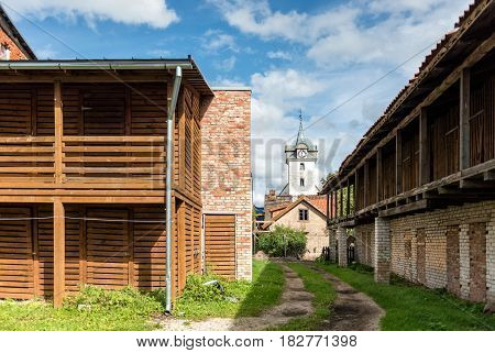 Yard with wood sheds. In the distance can be seen the church tower.