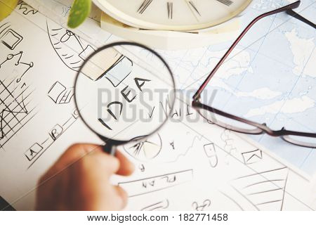 man hand magnifyinidea writng on paper background