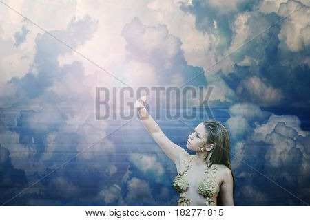 Beautiful girl among the clouds looking towards the light