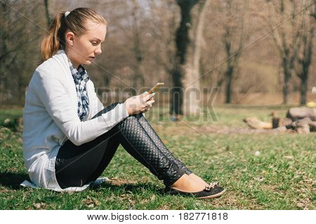 Beautiful young European girl sits on the grass in the park and uses a smartphone, concepts of using gadgets in a natural environment