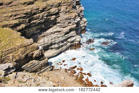 Aerial top view of sea waves hitting rocks next to beach . Cape of Good Hope, Cape Town, South Africa.