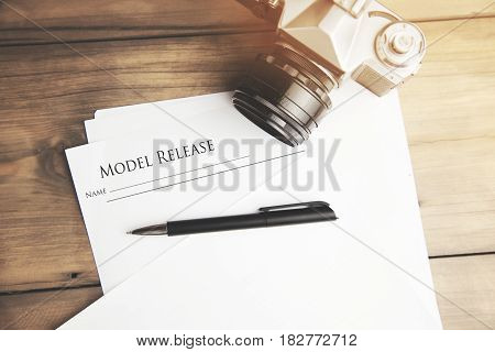 model releasecamera and pen on wooden table