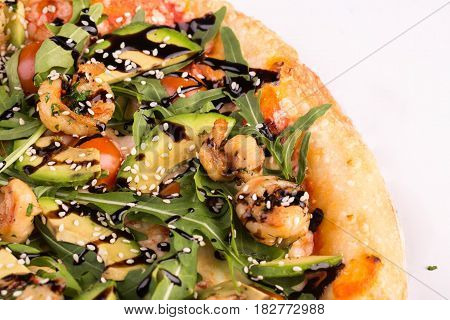 piece of pizza with shrimps and avocado, with tomato sauce and arugula