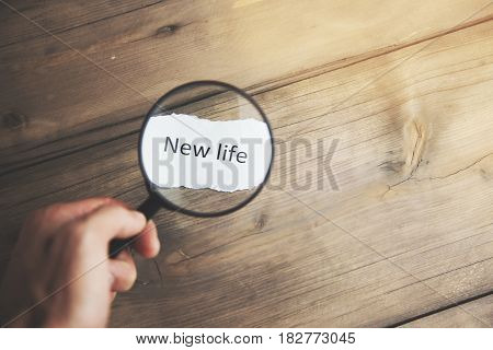 man hand magnifying glass with words new life