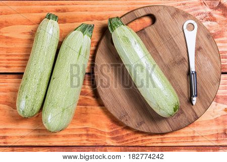 Flat Lay Fresh Raw Zucchini On The Wooden Background With Knife Peeler