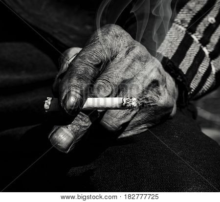 Old man smoking. Closeup hand with cigarette