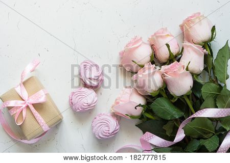 Pink rose gift box and dessert at white stone table. Top view. Mothers day background.