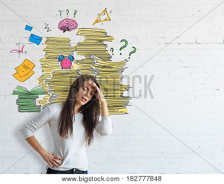 Tired young european girl on brick background with paperwork piles. Workload concept