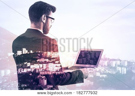 Side view of businessman using laptop with blank screen on creative city background. Double exposure