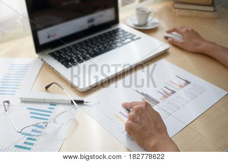 Business adviser analyzing financial figures denoting the progress in the work of the company with laptop chart board and tablet team of business selective focus and soft focus.