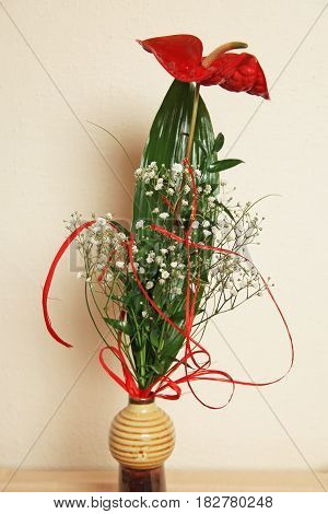 bouquet with red anthurium, small white flowers and green leaves in a vase