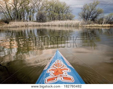 FORT COLLINS, CO - April 19, 2017:  Paddling a stand up paddleboard by Starboard  on a small lake with early spring lake scenery.