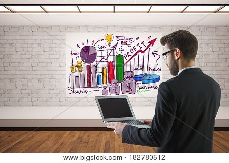 Young businessman using empty laptop in interior with sketch. Online business concept. 3D Rendering