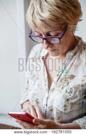 Mature confident female in glasses looking at screen of smartphone.