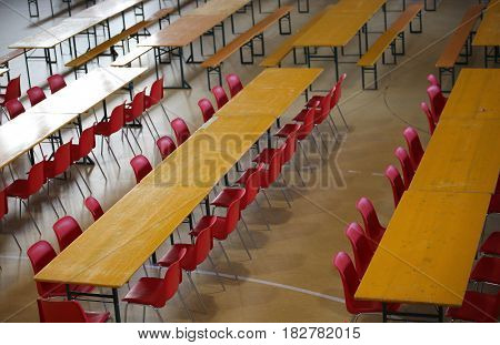 table with red chairs in a wide lunch room in a school