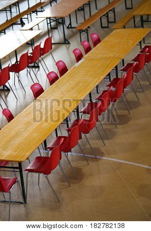 many long table with red chairs in a wide classroom