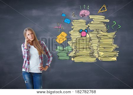 Thoughtful young european girl on chalkboard background with paperwork piles. Workload concept