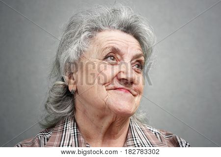 Smile and thinking elderly woman face on a grey background