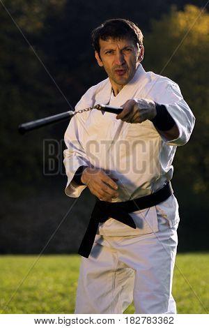 Ninja in white kimono is practicing martial arts with nunchaku outdoors.
