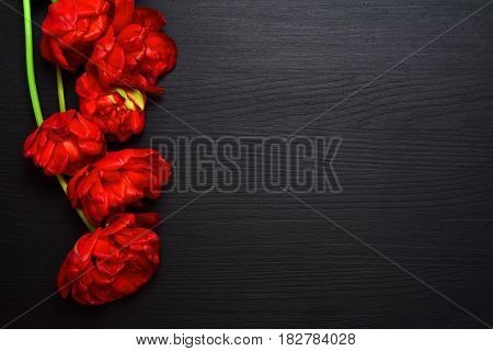 bouquet of bright red fluffy tulips on a black wooden surface a blank space on the right