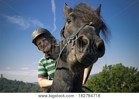 Beautiful young woman rides her black Horse - Outdoor Shot
