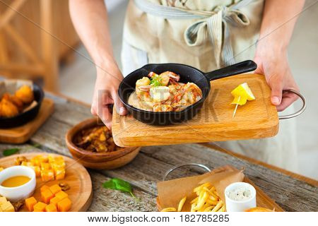 Long-haired beautiful woman in apron holds a tray with food in her hands. Waiter serves food. Food and drink concept