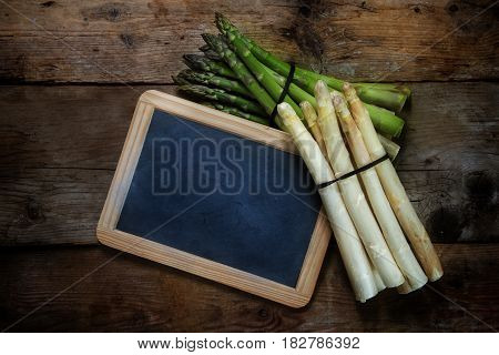 Green and white asparagus and a blank blackboard on a rustic wooden background top view from above copy space selective focus