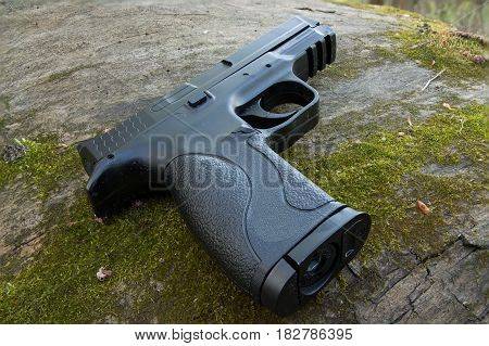 Black gun. Large stumps and moss. Tactical gun. Military gun. Sport shooting.