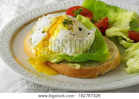 Poached egg with running yolk on baguette slice with salad and tomatoes on a white plate delicious breakfast or snack closeup selective focus narrow depth of field