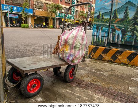 Taipei Taiwan - October 08 2016: Small luggage cart with a bag of garbage on a Taiwan street